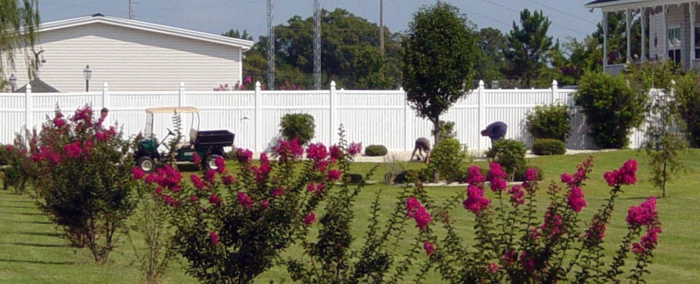 flowers in front of vinyl fence
